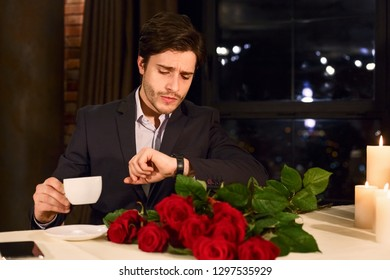 Man with flowers waiting girlfriend in restaurant nervous, drinking coffee, checking time