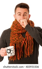Man with flu and fever wrapped in scarf holding cup of healing tea and coughing isolated over white.