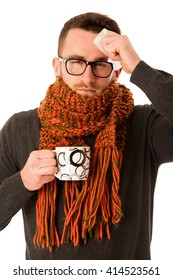 Man with flu and fever wrapped in scarf holding cup of healing tea and handkerchief isolated over white.