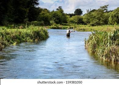 Man fly fishing casts on Irish river