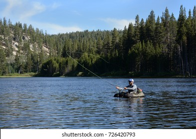 A man fly fishing from a float tube on a small lake.