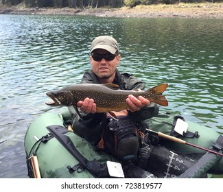 Man fly fishing from a pontoon or float tube with his catch, large trout fish (Brook Trout hybrid with Lake Trout, called Splake)