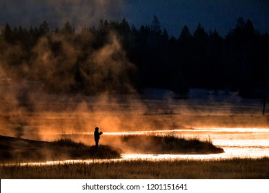 Man flyfishing in early morning light on a misty river with golden sunlight