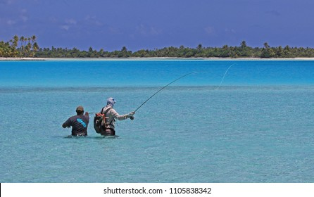 Man flyfishing with a guide in turquoise ocean in French Polynesia