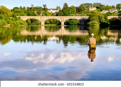 Man fly-fishing on the River Tweed with the iconic Kelso Bridge at the background. Kelso, Scottish Borders, Scotland, UK