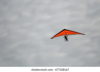 Man flying from hang glider on a cloudy day./ Hang gliding flight./ Man flying from hang glider on a cloudy day.