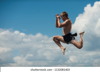Man flying kick in sky background. Martial arts composition