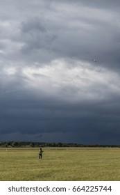 A man flying a kite beneah an overcast sky