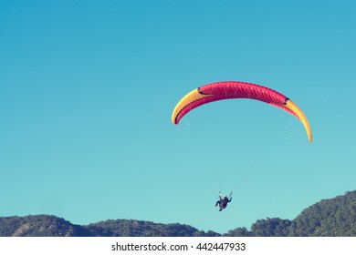 Man flying a paraglider in the sky over the mountains