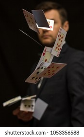 Man with flying playing cards in suit with dark background