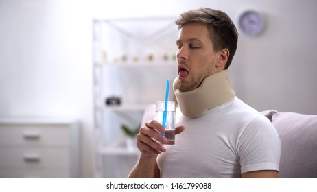 Man in foam cervical collar trying to drink glass water with straw, poor attempt