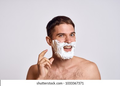 man with foam for shaving on a light background, beauty, care