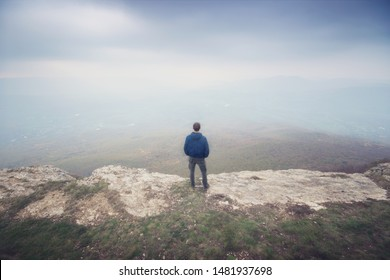 Man in fog in mountain looking to infinity. Conceptual scene.