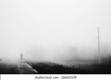 Man in fog. Silhouette of man walking on misty village road. Loneliness, nostalgia, sad mood. Black and white photo