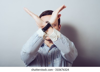 The man folded his arms across his chest. Gesture cross X, stop, you can not ban, serious, unhappy, listening intently. On a gray background