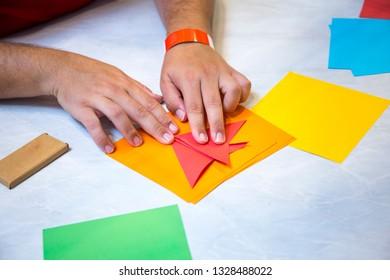 A man folding blue color paper