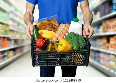man with food box in hands at grocery store