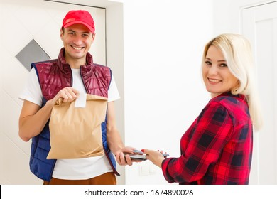 Man food delivery holding paper bag in an apartment