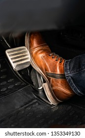 Man foot on the break pedal of a car.