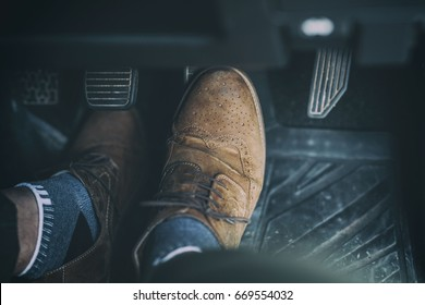Man foot press the break  pedal of a car.