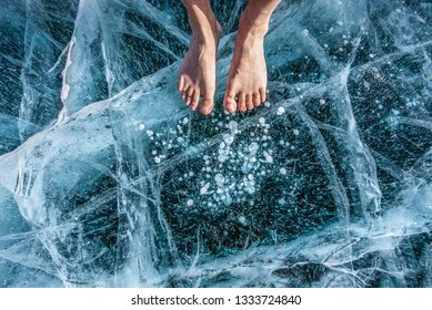 Man foot spa treatment on cracks surface of the natural ice in frozen water at Olkhon Island, Baikal lake, Russia