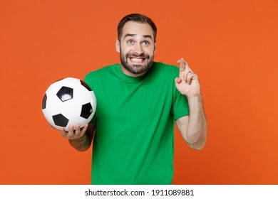 Man football fan in green t-shirt cheer up support favorite team with soccer ball wait for special moment keeping fingers crossed make wish isolated on orange background. People sport leisure concept