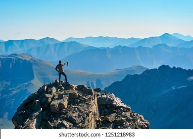 The man in the foreground stands on a cliff and enjoys the view of the sunrise in the mountains.