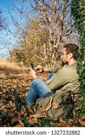 Man in the forest looks at the phone