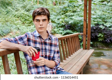 Man in the forest in wooden summerhouse with red paper cup