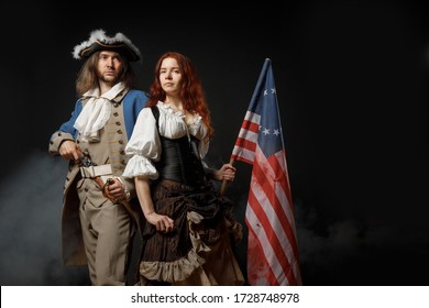 Man in form of officer of United States War of Independence and girl in historical dress of 18th century. July 4 is US Independence Day. Studio photo on black background