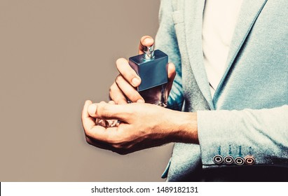 Man in formal suit, bottle of perfume, closeup. Fragrance smell. Men perfumes. Fashion cologne bottle. Man holding up bottle of perfume. Men perfume in the hand on suit background. Copy space.