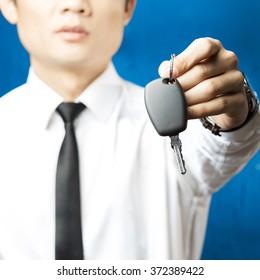 Man in formal suit holding car keys