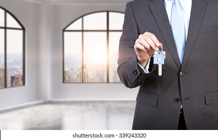 A man in formal suit holds a key in a modern loft panoramic apartment or office. Rent or buy new home or office. New York view. A sunset.