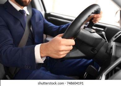 Man in formal suit on driver's seat of car