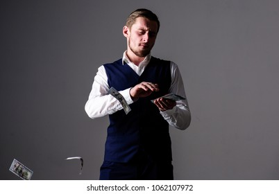 Man in formal wear, businessman throwing money on grey background. Rich and carefree concept. Successful entrepreneur on arrogant face wasting money. Banknotes, cash dollars fly in air near guy.