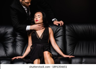 man in formal wear choking sexy woman isolated on black