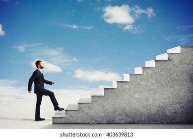 Man in a formal wear climbing concrete stairs in a light cloudy sky, side view