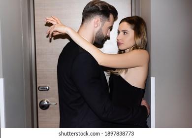 Man in formal wear hugging seductive girlfriend in dress in hotel room