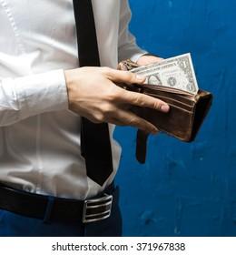 A man in formal wear opening his wallet