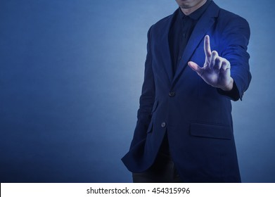 man in formal wear touching empty virtual glass over dark blue background,business concept