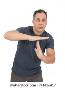 Man forms the letter T with his hand. Symbol to ask for time. Interval, pause, interrupt. He is bald, has overweight and wears dark gray T-shirt. Isolated. White background.