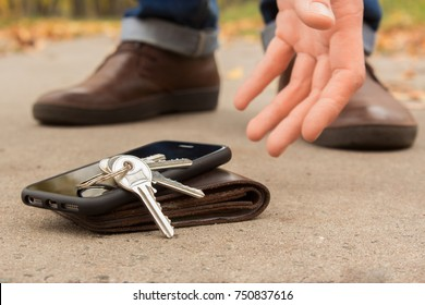 The man found the keys, phone and wallet with money. Men are standing and only the legs and shoes are not in focus. The man raises his hand keys, phone and wallet on the ground