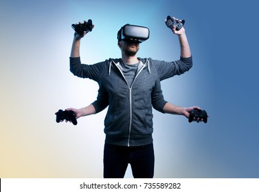 Man with four arms holding game controllers and wearing VR goggles on head . Photo manipulation, of modern gamer  /skillful gamer, expert