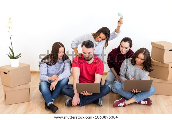 Man with four girls sitting on the floor of a new home with a laptop on a cardboard box