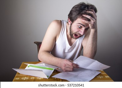 Man freaking out over his expenses, looking at bills worried