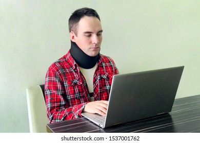 Man freelancer in a cervical collar neck brace working from home. neck support on the prosthesis. fracture of the cervical vertebrae. Treatment of neck pain.