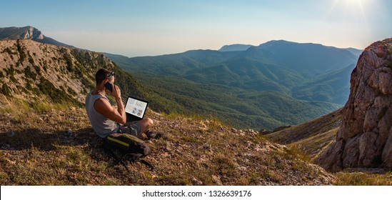 man freelancer sit with laptop, call by cellphone, on beauty mountains landscape, freelanc concept