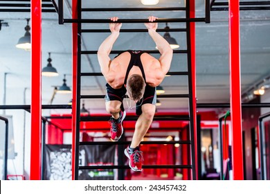 Man at freestyle Calisthenics training in gym on frame