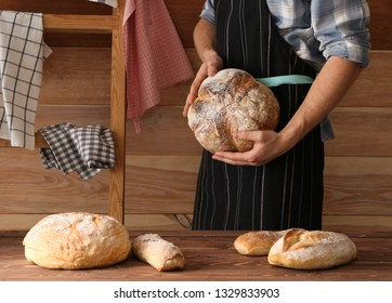 Man with freshly baked bread in kitchen