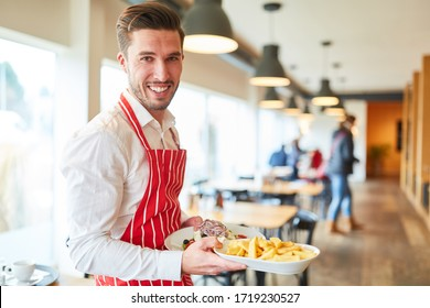 Man as a friendly waiter in training serves food in the restaurant